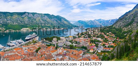 The red roofs of the old Kotor with the luxury yachts and the cruise liner in port, Montenegro. - stock photo