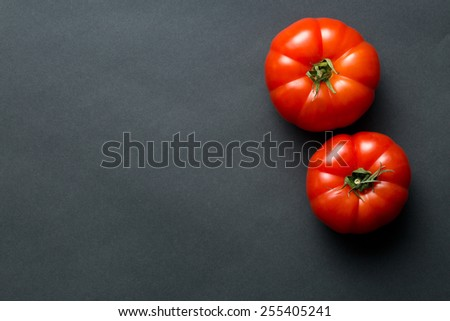 the red tomatoes on black background - stock photo