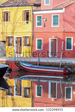 The reflection in the water channel of the colored houses - Burano, Venice, Italy