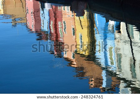 The reflection of a colorful houses in water canal, Burano island, Venice,  landmark of Veneto region, Italy - stock photo