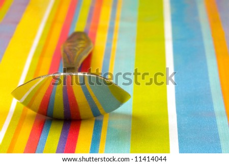 The reflection of stripped paper on the bottom of a spoon - stock photo