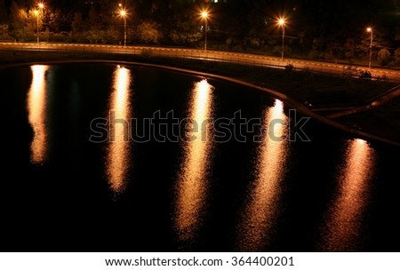 The reflection of the streetlights in the water at night.