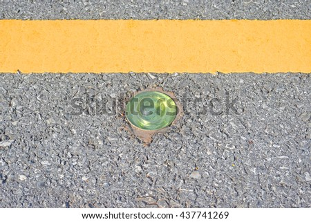The reflective ball glass road stud and yellow line on the asphalt road  - stock photo