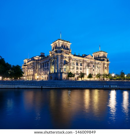 The Reichstag building (Bundestag) with reflection in river Spree at night