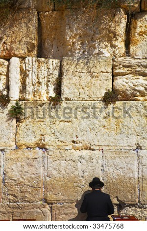 The religious Jew praying at the Western wall of the Jerusalem temple - stock photo