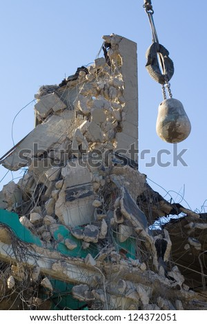 The remains of a demolished factory building, with wrecking ball hanging amidst the wreckage. - stock photo
