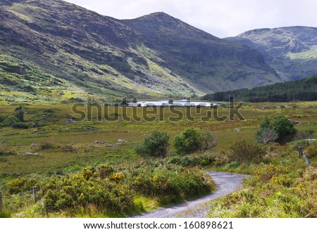 The remote and peaceful Black Valley, close to the Gap of Dunloe near Killarney, County Kerry, accessible by a single track road. Typical Irish country scene of green grass and rugged blue mountains. - stock photo