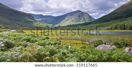 The remote Black Valley in the Kerry mountains, south west Ireland, accessible by a single track road, where bracken grows beside the lake and cloud shadows drift across the blue hills beyond. - stock photo