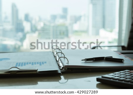 The report analyzes the growing business and pen  on desk of financial adviser with city in background.   - stock photo