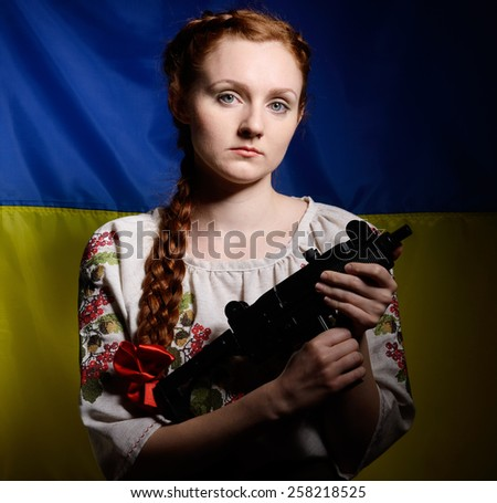 The resolute young woman is holding a uzi gun against the national Ukrainian flag. She is wearing a shirt embroidered. Her red hair are plaited with a red ribbon.  - stock photo