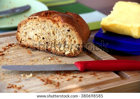 The rest of an already sliced sweet yeast bread on a cutting board. Surrounded by a piece of butter and an eating plate.