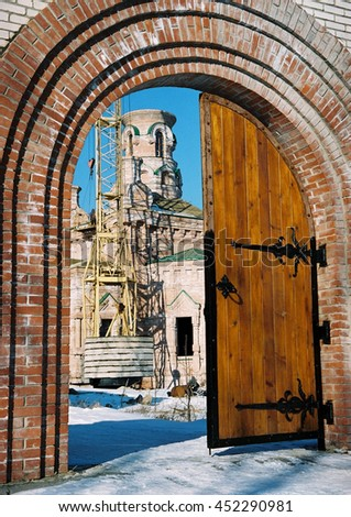 The restoration of the Church,of the temple.Wooden,brown door with black handles.Arch,the passage of red brick.The crane lifts the load.Blue sky, snow, winter.Windows without glass. Ukraine,Kiev. - stock photo
