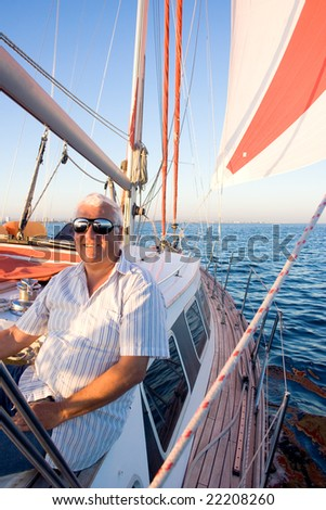 The retired man enjoy the sailing on his boat. - stock photo