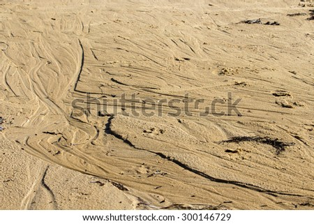 The retreating tide leaves a delicate pattern on the wet sandy shore at Ocean Beach Bunbury, Western Australia in mid winter. - stock photo
