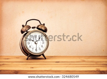 the retro and vintage style of Old fashioned the alarm clock on wooden table - stock photo