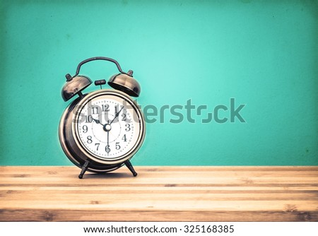 the retro and vintage style of Old fashioned the alarm clock on wooden table with retro blue concrete background - stock photo