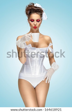 The retro photo of a vintage pin-up girl drinking a morning cup of tea, wearing a corset and stylish makeup. - stock photo