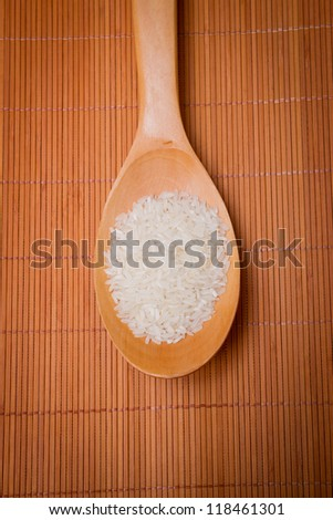 the rice in a rice scoop on on bamboo mat