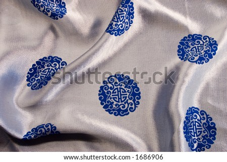 The rich blue and silver silk background with chinese or japanese emblems and design provides a colorful cultural backgound, texture or brush. - stock photo