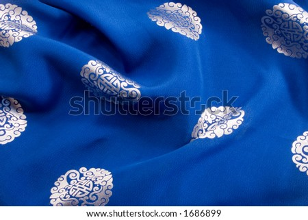 The rich blue silk background with chinese or japanese emblems and design provides a colorful cultural backgound, texture or brush. - stock photo