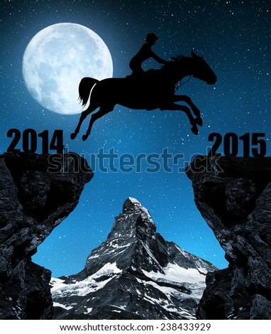The rider on the horse jumping into the New Year 2015. In the background Matterhorn. - stock photo