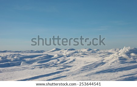 The ridges in the sea, snowy hills on a frozen plain - stock photo