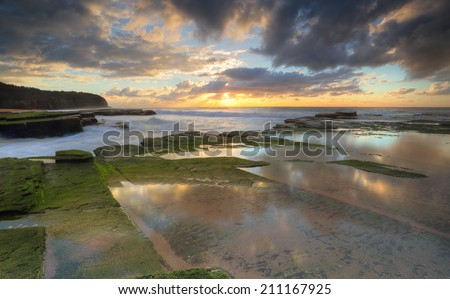 The riising sun hides behind some clouds.  The Turrimetta coastline and reflectios during winter Sydney Australia - stock photo