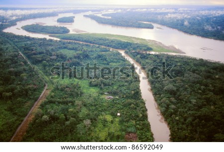 The Rio Napo in the Ecuadorian Amazon viewed from the air, Rio Jivino in foreground and a road built by oil companies bringing colonists who cut the foreground forest - stock photo