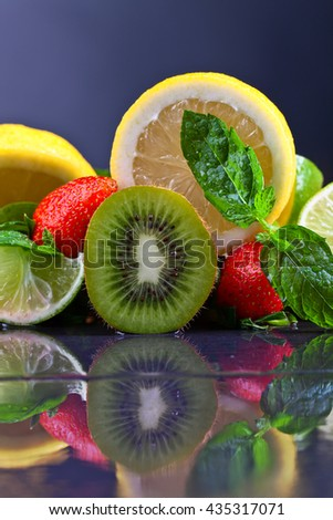 The ripe juicy fruits and peppermint leaves on a dark background - stock photo