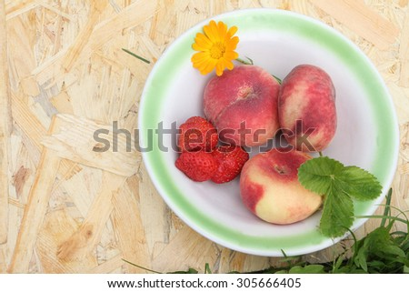 The ripe peaches and strawberry lying in a plate on a wooden basis in a garden - stock photo