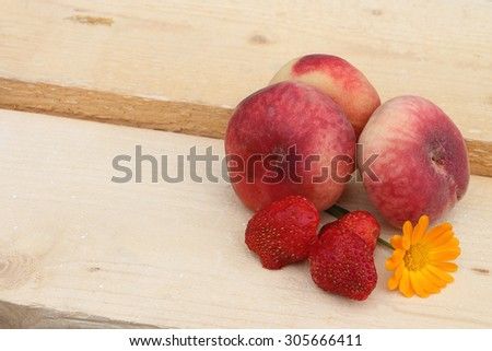 The ripe peaches and strawberry lying on a wooden basis in a garden - stock photo