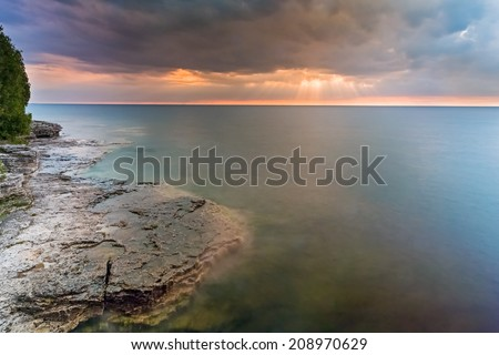 The risen sun shines rays through clouds over Lake Michigan at Door County, Wisconsin's Cave Point. - stock photo