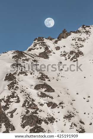 the rising of the full moon in the mountains - stock photo