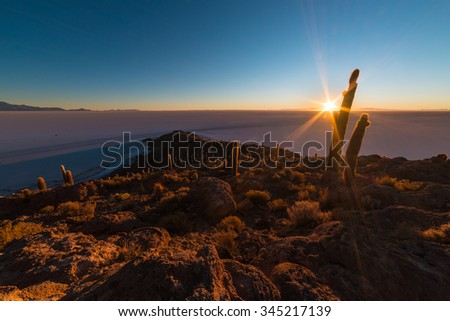 The rising sun at the horizon over the majestic Uyuni Salt Flat, among the most important travel destination in Bolivia. Wide angle in backlight from the Incahuasi Island with glowing rocks and cactus - stock photo