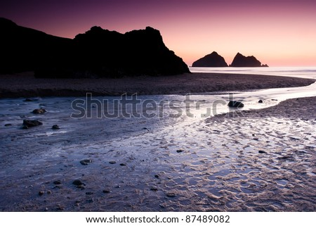 The river flowing down the beach during sunset at Holywell Bay Cornwall UK. - stock photo
