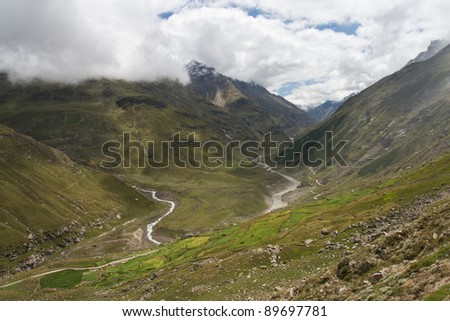 The river flows into the mountains, covered with green grass - stock photo