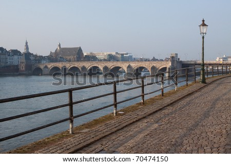 The river Meuse with the city of Maastricht and one of its landmarks the Saint Servatius Bridge in the background. - stock photo