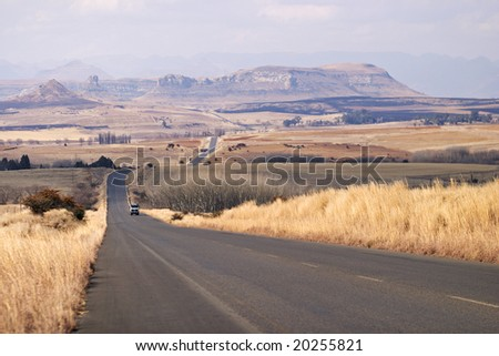 The road between Ficksburg and Clarens in South Africa runs through rolling winter farmlands. - stock photo