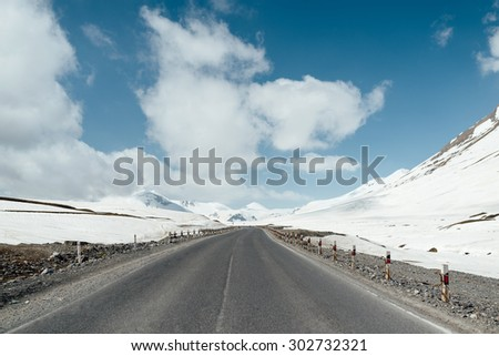 The road between magnificent snow mountains - stock photo
