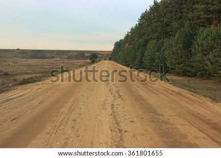 The road leading to the forest in the green, on the other side of the field. On top of the bridge with a roadway. - stock photo