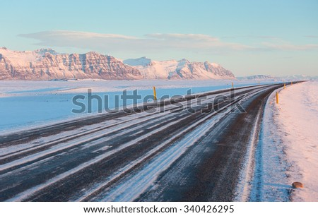 The road on a sunny winter day along  the snow-capped mountains. The Ring Road (Route 1) of Iceland, between Hof and Jokulsarlon. South of Iceland - stock photo