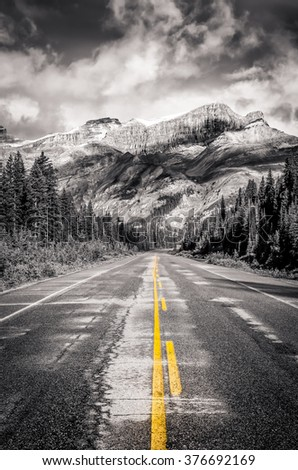 The road on Icefields parkway in Canadian Rockies in black & white with selective colorization and filtered style, Banff and Jasper NP - stock photo