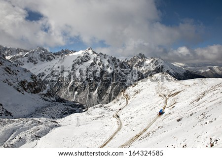 The road spirals up the snow mountain. - stock photo