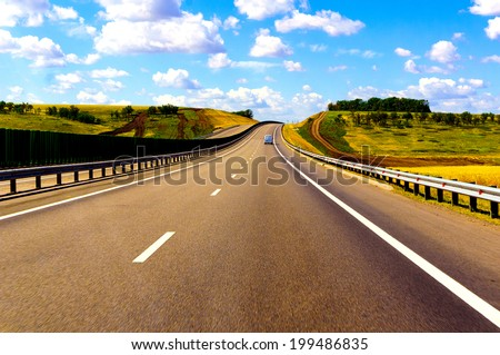 The road through the green fields and clouds on blue sky in hot summer day  - stock photo