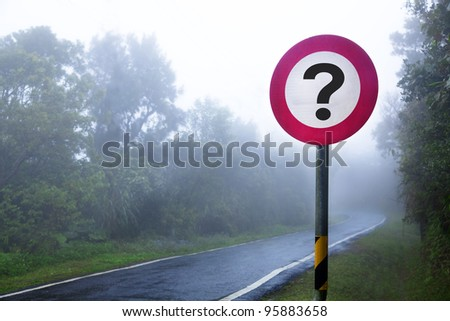 The road to the fog forest and question sign - stock photo