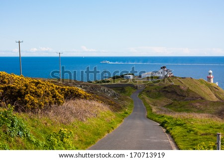 The road towards the Baily Lighthouse on Howth cliffs in Ireland on a sunny day - stock photo