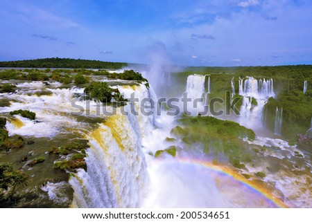 The roaring waterfalls in South America - Iguazu. Blanker jet fall between green jungle. Magnificent rainbow shines in the mist - stock photo