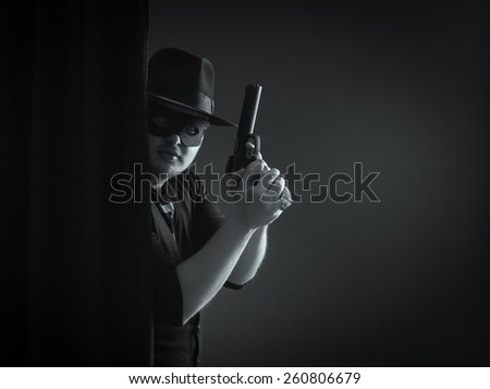 The robber or bandit in a mask shoots a gun. - stock photo