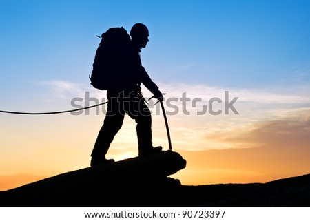 The rock-climber walking on mountain top on decline - stock photo