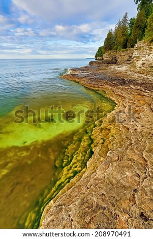 The rocky and rugged coastline of Door County, Wisconsin's Cave Point displays colorful pools under a cloudy blue morning sky. - stock photo